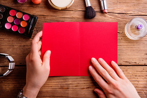 Hands of unrecognizable woman holding empty red greeting card. Various make up products. Studio shot on wooden background. Copy space.