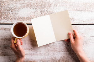 Hands of unrecognizable woman holding empty sheet of paper. Cup of tea and eyeglasses. Studio shot on white wooden background. Flat lay, copy space.