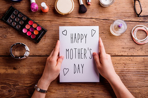 Hands of unrecognizable woman holding Mothers Day greeting card and various make up products. Studio shot on wooden background.