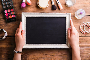 Hands of unrecognizable woman holding white picture frame with black board in it and various make up products laid on table. Studio shot on wooden background. Flat lay, copy space.
