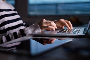 Hands of unrecognizable woman sitting at desk at night working on laptop late at night. Close up.
