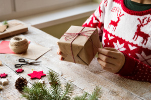 Hands of unrecognizable woman wrapping and decorating Christmas present. Studio shot.