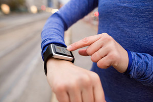 Hands of unrecognizable young woman running in the city, using a fitness app on her smartwatch for tracking weight loss progress, running goal or summary of her run. Rear view.
