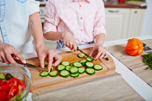 Hands of woman and little girl cutting fresh cucumber