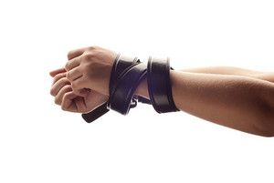 Hands of woman are tied up by belt.