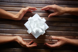 Hands of woman giving box with Christmas present to her friend on wooden background