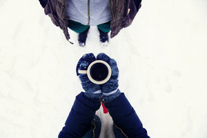 Hands of young woman holding a cup of coffee outside in snow