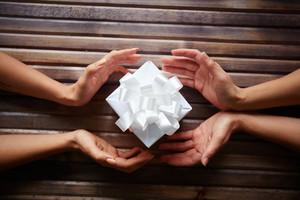 Hands surrounding a little gift box