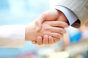 Handshake of business partners after signing contract