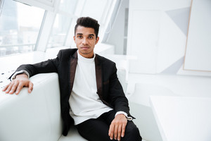 Handsome african business man in black suit sitting on sofa in office and looking at camera
