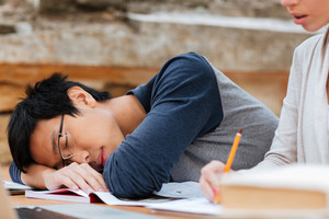 Handsome asian young man in glasses sleeping on the lesson