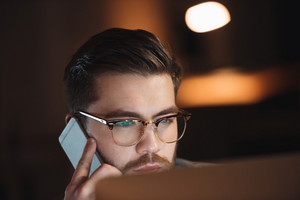 Handsome bearded designer dressed in shirt and wearing eyeglasses working late at night and talking by phone.