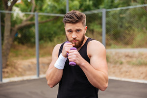 Handsome bearded sports man working out with small dumbbells outdoors