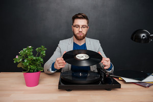 Handsome bearded young businessman in glasses sitting and using turntable and vinyl record