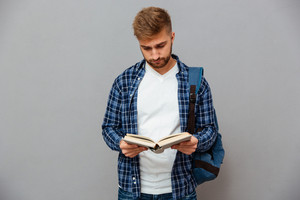 Handsome bearded young man in checkered shirt with backpack reading book isolated on a gray background