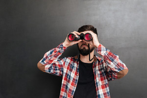 Handsome bearded young man in plaid shirt standing and looking through binoculars