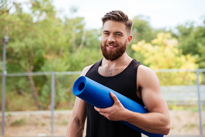 Handsome bearded young sportsman holding yoga mat and looking at camera outdoors
