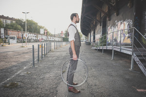 handsome big moustache hipster man holding old bicycle wheel in the city