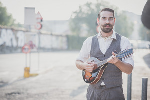 handsome big moustache hipster man playing mandolin in the city