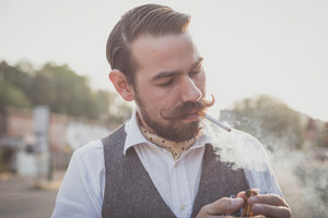 handsome big moustache hipster man smoking cigarette in the city