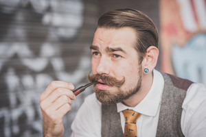 handsome big moustache hipster man smoking pipe in the city