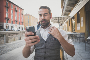handsome big moustache hipster man using smart phone in the city