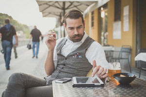 handsome big moustache hipster man using tablet sitting at the bar