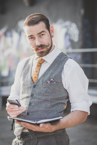 handsome big moustache hipster man with diary and smartphone in the city