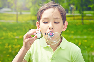 Handsome boy blowing soap bubbles in park