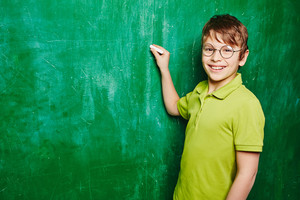 Handsome boy looking at camera while standing by blackboard