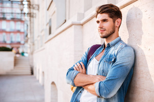 Handsome casual man standing with arms folded and leaning on the wall on the street