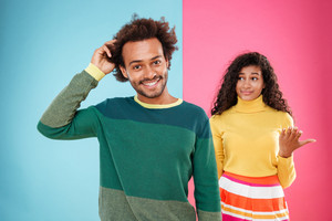 Handsome confident african young man standing in front of his girlfriend over colorful background