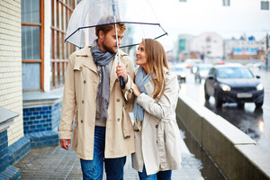 Handsome couple under the rain on the street