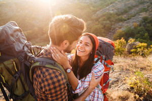 Handsome couple with backpacks in the mountains. eyes to eyes
