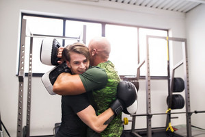 Handsome fit man boxing with his personal trainer, hugging at the end of the fight. Two athlete boxers sparred in boxing gym.