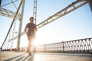 Handsome fit man running fast along big modern bridge at sunset light