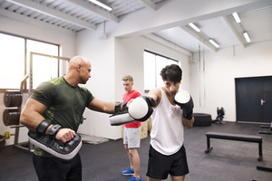 Handsome fit young man boxing with his personal trainer. Athlete boxers wearing boxing gloves sparred in boxing gym.