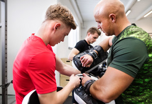 Handsome fit young man in gym with his personal trainer preparing for boxing, putting on boxing gloves.