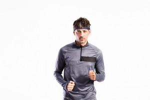 Handsome fitness man in gray sweatshirt jogging. Studio shot on gray background.