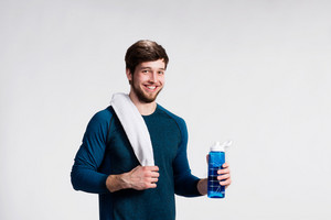 Handsome fitness man resting after working out, towel on his shoulder, holding water bottle. Studio shot on gray background.