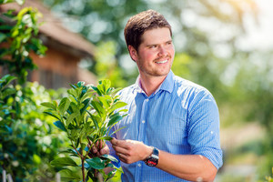 Handsome gardener with little tree against green sunny nature