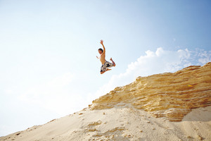 Handsome guy in jump over sandy beach against sky
