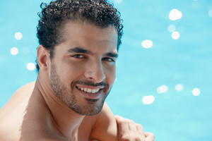 Handsome happy young hispanic man smiling and relaxing near hotel pool. Horizontal shape, head and shoulders, copy space