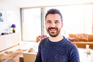 Handsome hipster businessman in blue long sleeved t-shirt, working from home, taking a break