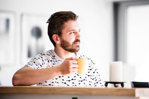 Handsome hipster businessman working from home, taking a break, drinking coffee