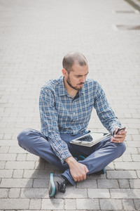 handsome hipster casual multitasking modern man using tablet in the city