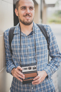 handsome hipster casual multitasking modern man with vintage camera in the city