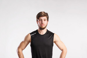 Handsome hipster fitness man in black sleeveless shirt. Studio shot on gray background.
