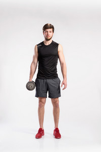 Handsome hipster fitness man in black sleeveless shirt working out with dumbbell. Studio shot on gray background.