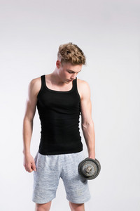 Handsome hipster fitness man in black tank top shirt holding a dumbbell. Studio shot on gray background.